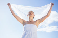 Pretty blonde in white dress holding up shawl on the beach Stock Photo