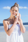 Pretty blonde in white dress listening to conch on the beach Royalty Free Stock Photography