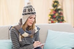 Pretty blonde with winter hat on writing on her notebook Stock Photos