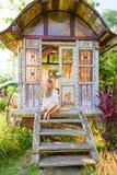 Pretty blonde woman and antique gypsy caravan 3. Pretty blonde woman sitting on the steps of an antique gypsy caravan at sunset royalty free stock image