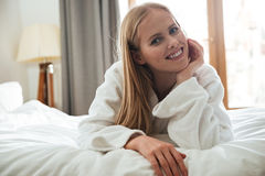 Pretty blonde woman in bathrobe looking camera. Pretty smiling blonde woman in bathrobe lying on bed and looking camera at home Stock Images