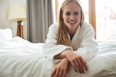 Pretty blonde woman in bathrobe looking camera Royalty Free Stock Photography