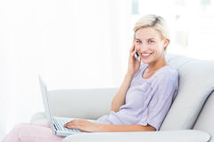 Pretty blonde woman calling on the phone and using her laptop. In the living room Stock Images