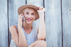 Pretty blonde woman calling on the phone. On wooden background Stock Photo
