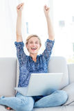 Pretty blonde woman cheering on the couch Royalty Free Stock Image