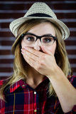 Pretty blonde woman covering her mouth with her hand Stock Images