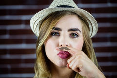 Pretty blonde woman doing a moustache with her finger Stock Photography