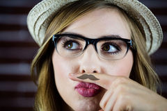 Pretty blonde woman doing a moustache with her finger Stock Photo