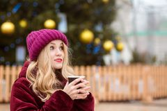 Pretty blonde woman drinking coffee near the Cristmas tree on th Royalty Free Stock Images
