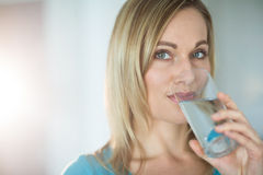 Pretty blonde woman drinking a glass of water Royalty Free Stock Images