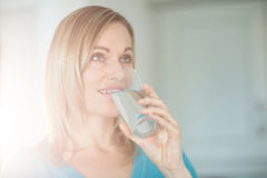 Pretty blonde woman drinking a glass of water Royalty Free Stock Photos