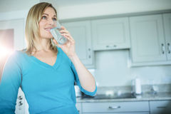 Pretty blonde woman drinking a glass of water Stock Photos