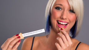 Pretty Blonde Woman Eats Fortune Cookie Showing Message Stock Photography