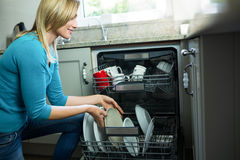 Pretty blonde woman emptying the dishwasher. In the kitchen stock photography