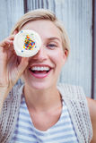 Pretty blonde woman grimacing with cupcake Royalty Free Stock Image