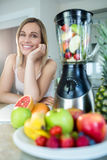 Pretty blonde woman happy to prepare a smoothie Stock Photography
