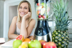 Pretty blonde woman happy to prepare a smoothie Royalty Free Stock Image