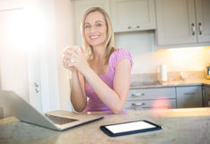 Pretty blonde woman having coffee and using laptop Stock Photo