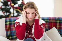 Pretty blonde woman having a headache on the sofa Stock Photos