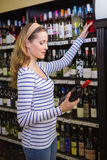 Pretty blonde woman holding a bottle of red wine Royalty Free Stock Photo