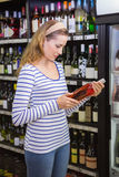 Pretty blonde woman holding a bottle of red wine Stock Photo