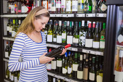Pretty blonde woman holding a bottle of red wine Stock Photography