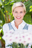 Pretty blonde woman holding bunch of flowers Stock Photo