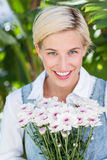 Pretty blonde woman holding bunch of flowers Royalty Free Stock Photography