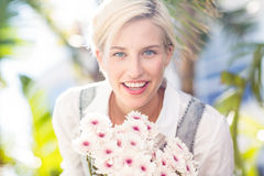 Pretty blonde woman holding bunch of flowers Royalty Free Stock Photos