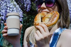 Pretty blonde woman holding cup of coffee and sweet pretzel in a stock photos
