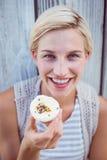 Pretty blonde woman holding cupcake Stock Photo
