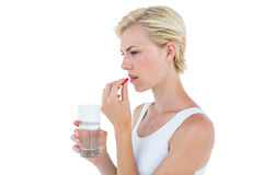 Pretty blonde woman holding glass of water and ready to swallow red pill Royalty Free Stock Image