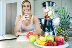 Pretty blonde woman holding her homemade smoothie Stock Photography