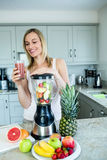 Pretty blonde woman holding her homemade smoothie Stock Photo
