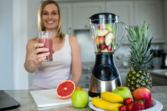 Pretty blonde woman holding her homemade smoothie Royalty Free Stock Image
