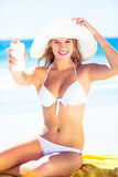 Pretty blonde woman holding sun tan lotion Royalty Free Stock Photo