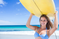 Pretty blonde woman holding surf board Stock Images
