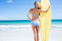 Pretty blonde woman holding surf board Stock Photo