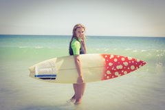Pretty blonde woman holding surf board Stock Photos
