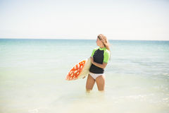 Pretty blonde woman holding surf board into the water Royalty Free Stock Image