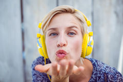 Pretty blonde woman listening music and blowing kiss Royalty Free Stock Images