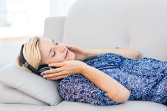 Pretty blonde woman listening music on the couch. In the living room Stock Photography