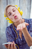 Pretty blonde woman listening music with her mobile phone and blowing kiss Royalty Free Stock Photos