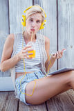 Pretty blonde woman listening music with her mobile phone and drinking orange juice Royalty Free Stock Images