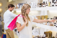 A pretty blonde woman looking at beauty product Royalty Free Stock Image