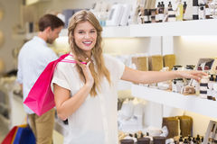 A pretty blonde woman looking at beauty product Stock Photo