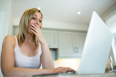 Pretty blonde woman looking at laptop Stock Images