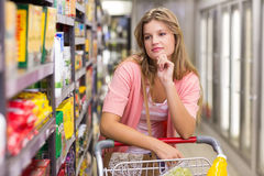 Pretty blonde woman looking at shelf Stock Images