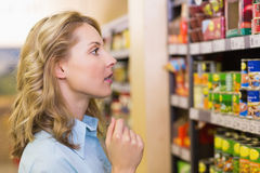 Pretty blonde woman looking at shelves. In supermarket Royalty Free Stock Photo