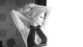 Pretty blonde woman looking via window